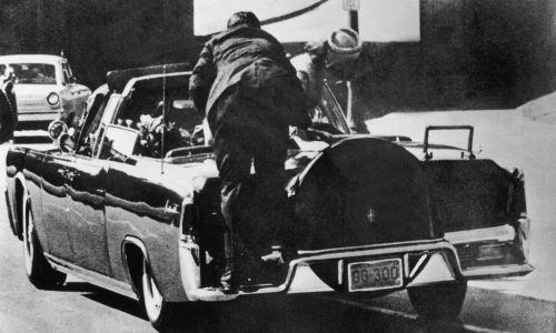 Zaraz po tym, jak John F. Kennedy, prezydent Stanów Zjednoczonych, został trafiony przez snajpera kulami w głowę, Jacqueline Kennedy wstaje w prezydenckim samochodzie, by podnieść ciało męża. Na pierwszym planie strażnik jeżdżący na tylnym błotniku pochyla się ku Kennedym. Fot. Keystone-France / Gamma-Keystone via Getty Images