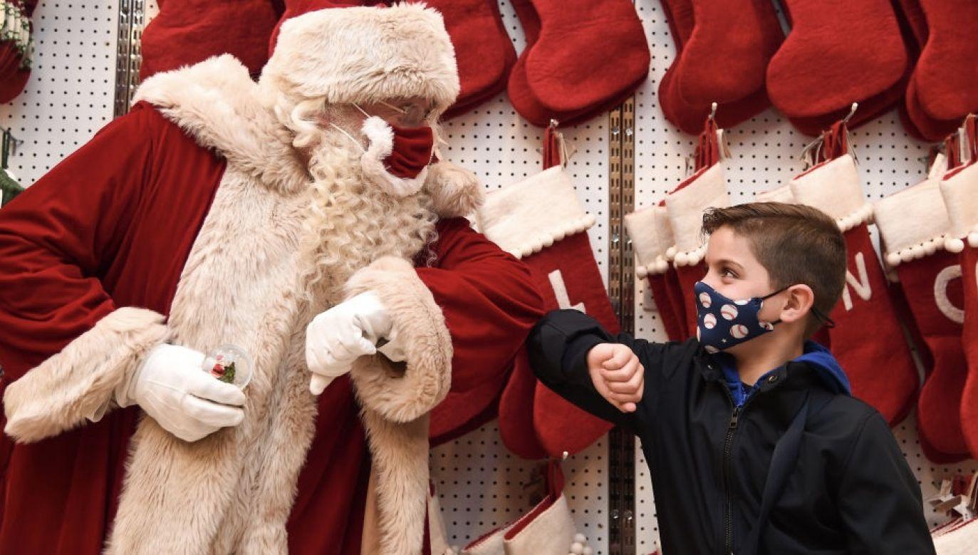 Skrzaty – pomocnicy Mikołaja – noszą maseczki, a sam Mikołaj przyjmuje gości w swoim biurze zza pleksi w kształcie piernika (fot. Eamonn M. McCormack/Getty Images)