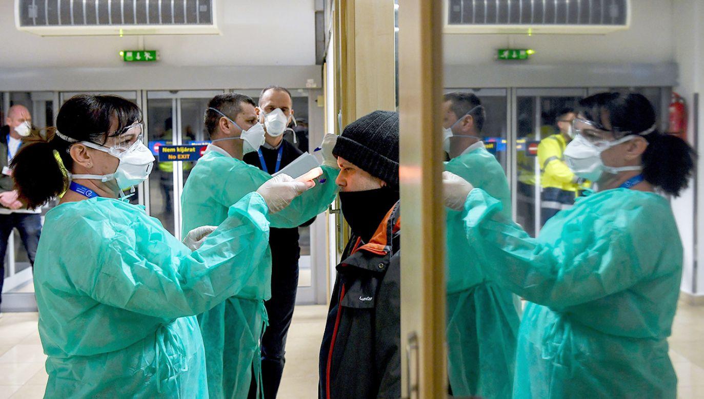 Ubranie się i zdjęcie odpowiedniego kombinezonu do pracy w laboratorium wymaga procedury zajmującej ok. 40 min. (fot. PAP/EPA/Zsolt Czegledi)