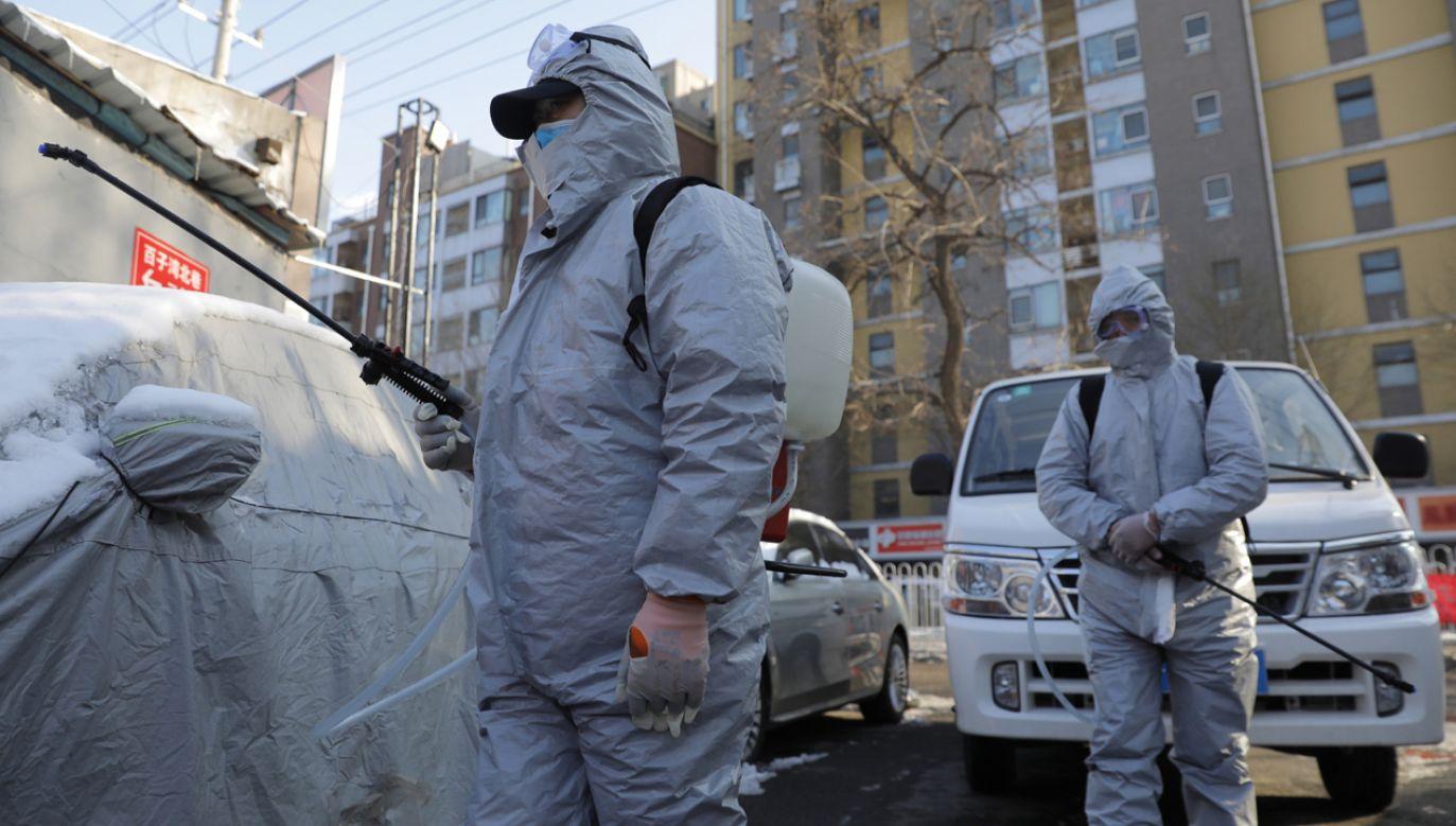Pracownicy ubrani w kombinezony ochronne dezynfekują dzielnicę mieszkalną w Pekinie (fot. PAP/EPA/WU HONG)