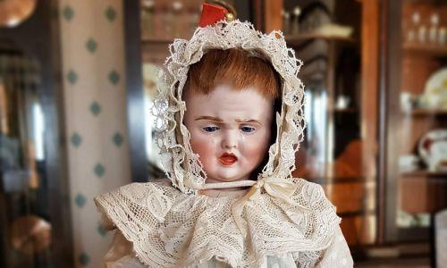 Lalka o trzech twarzach z berlińskiej wytwórni z przełomie XIX i XX wieku. Odzwierciedlała  trzy stany: sen, uśmiech  płacz. Widoczna była jedna, wybrana twarz, pozostałe ukrywał czepek, aż do przekręcenia głowy na inny stan. Lalka może przerażać. Została skrytykowana i szybko przestano ją produkować. Fot. Muzeum Zabawek w Kudowie Zdroju